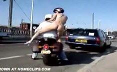 Garota nua em cima da moto na rua